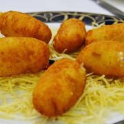 Croquetas de jamón sobre patatas paja